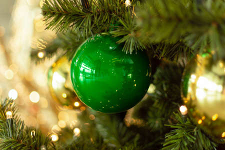 Decorated Christmas tree closeup. Green and golden christmas ornament balls and garland with golden lights. Winter holiday christmas tree decoration. Christmas greeting card. Archivio Fotografico