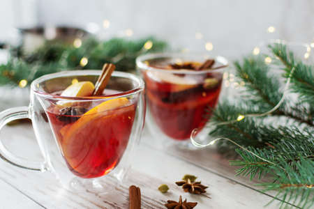 Christmas mulled red wine with spices and fruits over Christmas decorated background. Traditional hot drink made from red wine at Christmas time.
