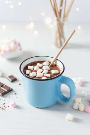 Hot chocolate with marshmallows in a blue enamel mug on white table. Hot cozy drink for autumn or winter season.