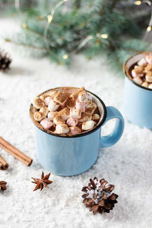 Spicy hot chocolate with cinnamon, star anise and marshmallows in enamel blue mug on white background with Christmas decorations. Christmas holidays and New Year beverage.