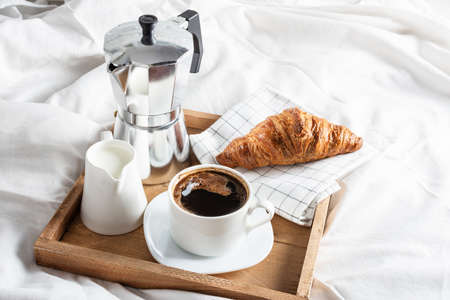 Wooden tray with cup of black coffee, jug of milk and croissant on white linen bed. Breakfast in bed with coffee and croissants.
