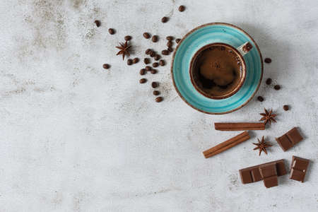A cup of coffee with cinnamon, anise spices and pieces of chocolate top view. Coffee cup and beans on grey background with copy space. Stockfoto