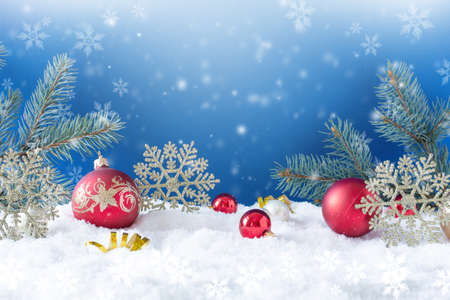 Christmas ornaments on snow over blue background with snowflakes. Winter Christmas greeting card.