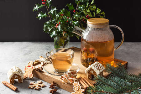 Glass teapot with blossoming tea and tea cup on grey table with Christmas gingerbread cookies. Christmas holiday tea ceremony. 免版税图像