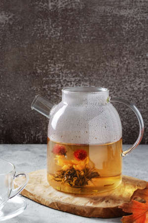 Glass teapot with blossoming tea on grey table. Vertical orientation.
