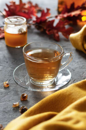 A glass cup of tea with honey on gray table. A cozy autumn morning with hot cup of tea. 免版税图像