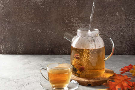 A steam of boiled water pouring into a glass teapot with blossoming tea. Autumn tea ceremony. 免版税图像
