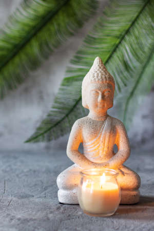 Buddha figure in meditation with burning candle on grey concrete background with palm leaf. Relaxation balance concept.
