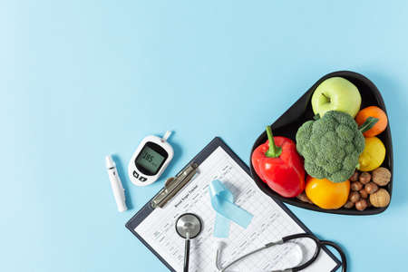Fresh vegetables and fruit with glucometer top view on blue background. Diabetic dieting concept.