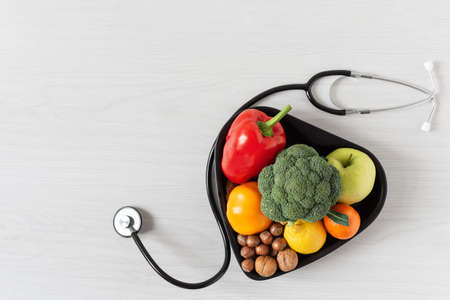 Heart shaped bowl with vegetables, fruits, nuts and stethoscope on white wooden background top view. Healthy eating concept.