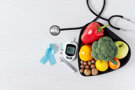 Fresh vegetables and fruit with glucometer top view on white wooden background. Diabetic dieting concept.