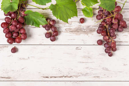 Bunch of ripe red grape with leaves on white wooden background top view. Grape fruit background with copy space for design.