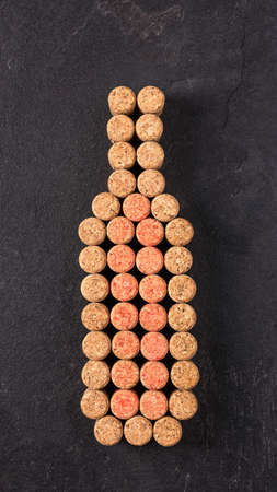 Creative red wine bottle made of wine corks on black background top view. Wine concept. Stock fotó