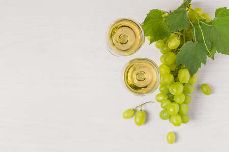 Glasses of white wine and white grape on wooden table top view. Wine composition with copy space for design.
