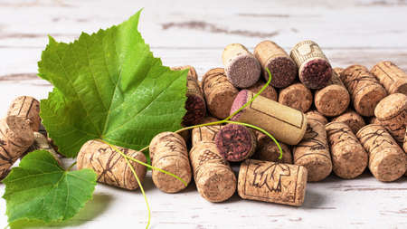 Wine corks with grape leaf over wooden background. Grape and wine concept.