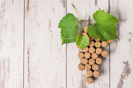 Creative grape bunch made of corks on wooden background top view. Wine concept.