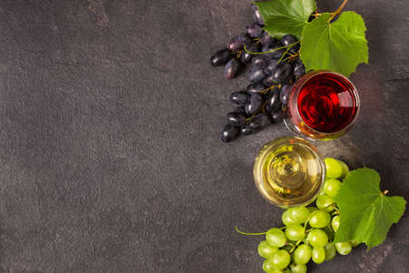 Glasses of red and white wine and variety of grape on black table top view. Wine composition with copy space for design.