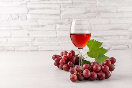 Glass of red wine and red grape on white wooden table. Wine composition with copy space for design.