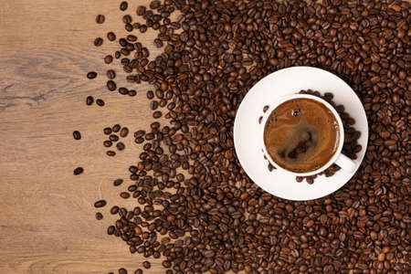 White coffee cup and saucer on wooden background with roasted coffee beans. Stock fotó