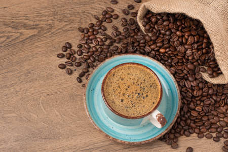 Coffee cup and saucer on wooden background with roasted coffee beans in a burlap sack.