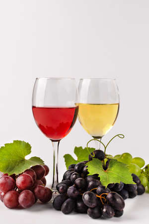 Wine composition with wine glasses and grape. Glasses of red and white wine and variety of grape on white background. Stock fotó