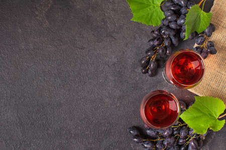 Glasses of red wine and blue grape on black background top view. Wine composition with copy space for design. Stock fotó