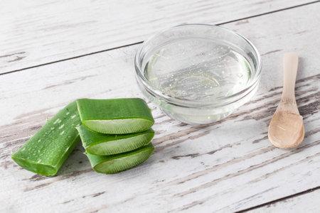 Aloe vera gel and aloe vera leaf on wooden background. Natural organic aloe vera cosmetics and herbal medicine concept. Stock fotó