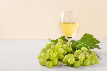 Glass of white wine and white grape on wooden table. Wine composition with copy space for design. Still life of wine and grape.
