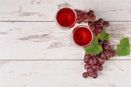 Glasses of red wine and red grape on white wooden background top view. Wine composition with copy space for design.