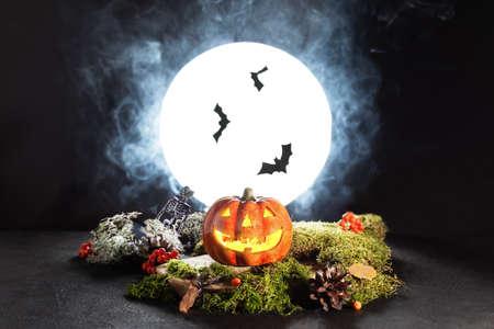 Halloween pumpkin Jack O' Lanterns glowing in spooky night over full moonlight. Halloween greeting card. Halloween scary still life. Stock fotó