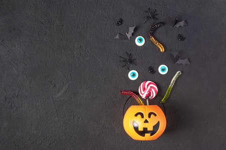Halloween pumpkin bucket with halloween candy and scary objects top view. Halloween background.