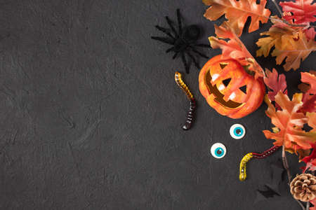 Halloween pumpkin Jack o Lantern and Halloween holiday candy and scary decorations on black background. Halloween background. Stock fotó