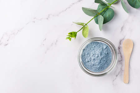 Dry facial blue clay powder in a bowl top view. Natural organic cosmetic clay for beauty treatment.