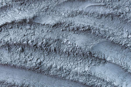 Texture of dry blue cosmetic clay with brushstroke top view. Abstract background of cambrian blue cosmetic clay or eye shadow.