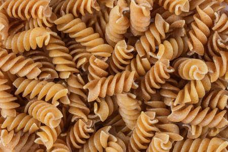 Organic raw gluten free buckwheat fusilli pasta background. Wholegrain gluten free macaroni. Food background.