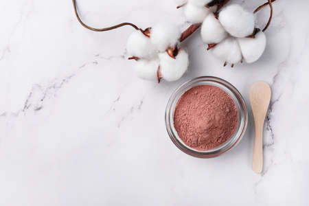Dry facial red clay powder in a bowl top view. Natural organic cosmetic clay for beauty treatment. Stock fotó