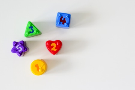 Colorful plastic shapes with numbers on a white background. Flat lay