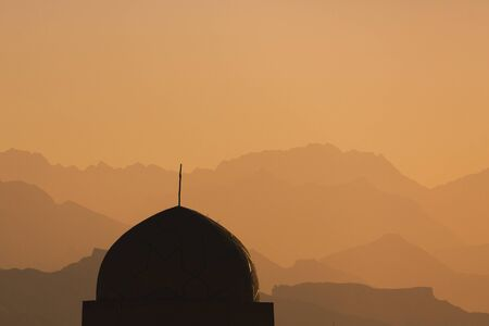 The dome of the mosque at sunset illuminated by the sun on an orange background of mountains