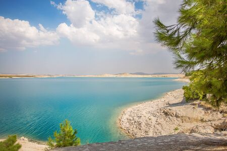 White coast with turquoise water and green pine trees and clouds. Reservoir on the Euphrates River