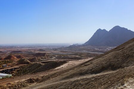 Industrial desert landscape with dumps of quarries, roads on the outskirts of the city