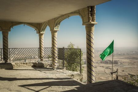 Desert city view from the mosque on top of the mountain in Qom city, Iran. Columns, fence, arcade and green flag on a background of blue sky. 免版税图像