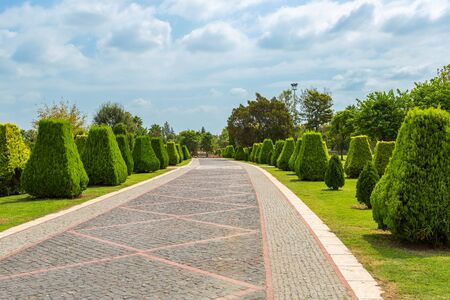 Cobbled walkway in a park with bright green clipped trees, blue sky and beautiful clouds. Regular Park in Adana, Turkey, Merkez Park