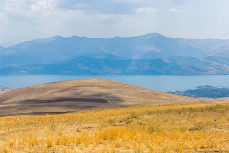 Van Lake in eastern Turkey, Bitlis Province. Blue lake surrounded by mountains. Beautiful landscape with yellow hills and blue sky