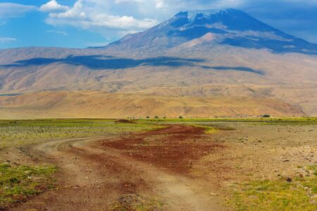 Dirt road at the foot of Mount Ararat. Panoramic view of Mount Ararat from Turkey, Eastern Anatolia. Beautiful landscape with a massif and blue sky. Mountain peak in the clouds Imagens