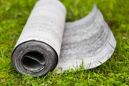 Roll of roofing felt close-up. Ruberoid on the green grass. A beautiful image of building material. Roof repair. Professional construction. Bituminous waterproofing