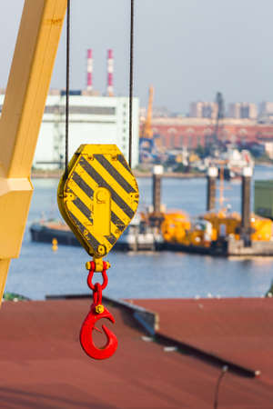 Loading crane with crook. Port unloading equipment. Industrial work. Red hook close up. Imagens