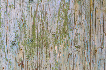 Old wooden surface with peeling paint. Abstract old background. Wood pattern with knots. Blue and green grunge background with scratches and cracks Reklamní fotografie