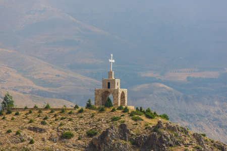 Chapel and cross in the mountains in Lebanon. Panoramic view of the Kadisha Valley. The place of the ancient Christian community. Beautiful Lebanese mountain landscape Archivio Fotografico