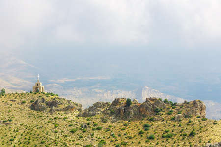 Chapel and cross in the mountains in Lebanon. Panoramic view of the Kadisha Valley. The place of the ancient Christian community. Beautiful Lebanese mountain landscape