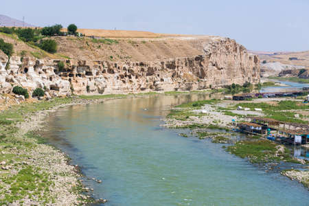 The view of the Tigris River valley in Hasankeyf town. Old cave houses in the rocks. Traditional cafes by the river, right in the water. Stock Photo